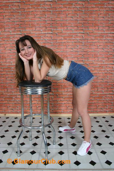 Honey B denim shorts and crop top posing with stool