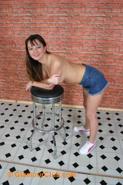 Honey B topless in denim shorts leaning over stool