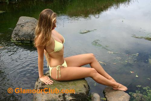 Maria Eriksson in yellow bikini sitting on rocks