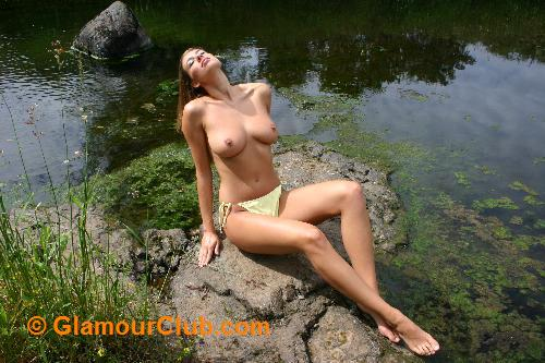 Maria Eriksson topless sitting on rocks