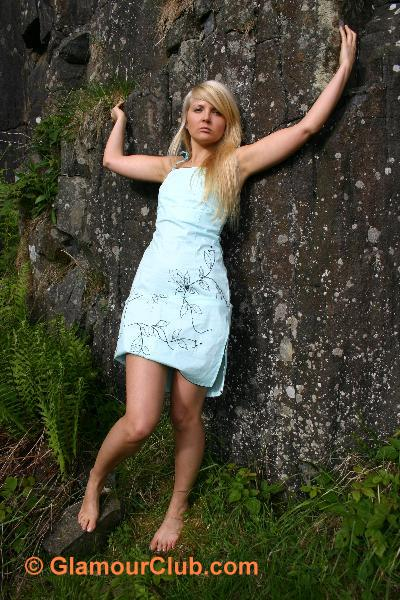 Oksana G in turquoise dress showing some leg
