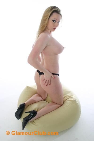 Shona topless kneeling on pouffe bum shot