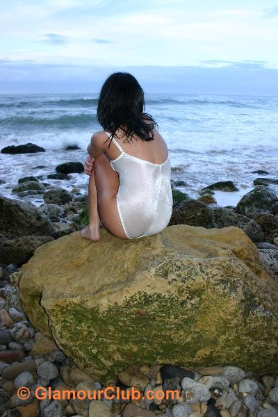 Jaki Leigh in white bodysuit on rock looking out to sea