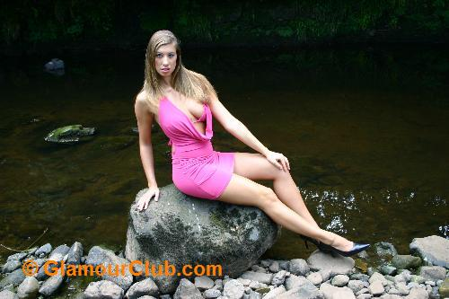 Maria Eriksson in pink dress sitting on rock