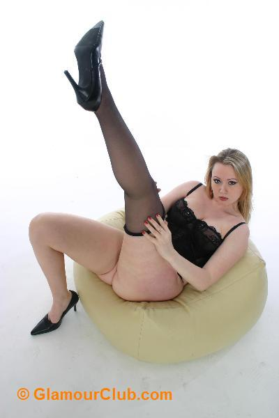 Shona in black undies lying on pouffe removing stocking